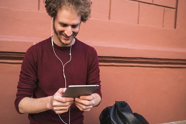 Retrato de joven guapo con su tableta digital al aire libre en la calle. tecnología y concepto urbano.