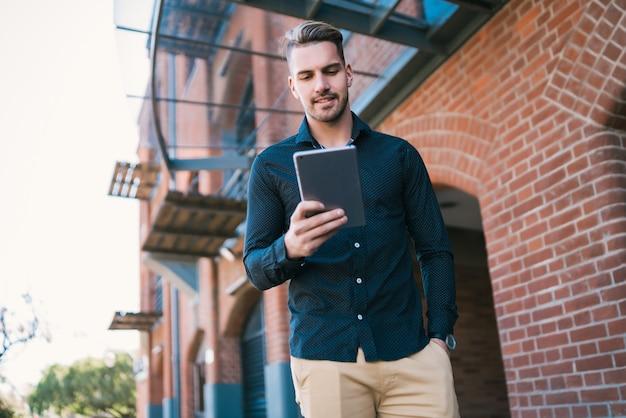 Retrato de joven guapo con su tableta digital al aire libre en la calle