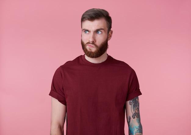 Retrato de joven guapo tatuado malentendido barbudo rojo en camiseta roja, se encuentra sobre fondo rosa, pensando en algo, mira hacia otro lado.
