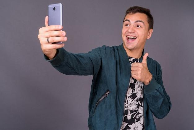 Retrato de joven guapo tomando selfie con teléfono móvil