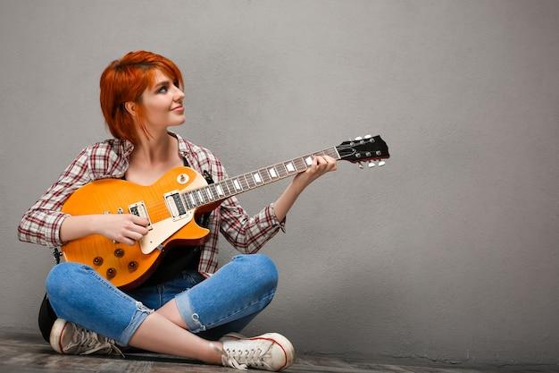 Retrato de joven con guitarra sobre fondo gris.