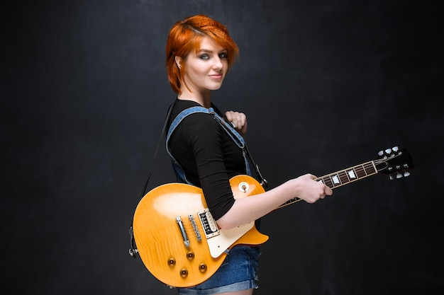 Retrato de joven con guitarra sobre fondo negro.
