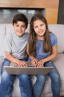 Retrato, de, joven, hermanos, usar la computadora portátil, en, sala