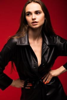 Retrato de una joven hermosa en un abrigo de cuero negro sobre una pared roja
