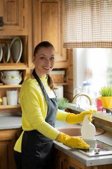 Retrato de joven hermosa ama de casa en delantal negro limpieza de encimera de cocina con detergente en aerosol, toallitas estufa con esponja