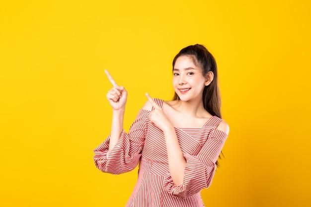 Retrato de joven hermosa asiática señalando con el dedo con ambas manos a un lado