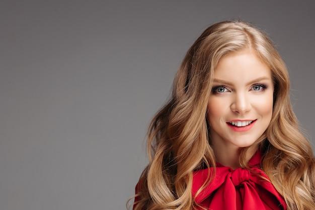 Retrato de joven hermosa en blusa roja con gran lazo.