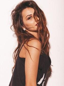 Retrato de joven hermosa chica hipster en moda verano negro camiseta. mujer despreocupada atractiva aislada en blanco. modelo morena con maquillaje y peinado