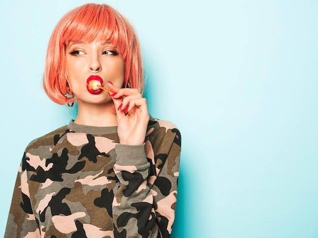 Retrato de joven hermosa chica mala inconformista en pantalones vaqueros de moda y aretes en la nariz ... modelo positivo lamiendo caramelos de azúcar