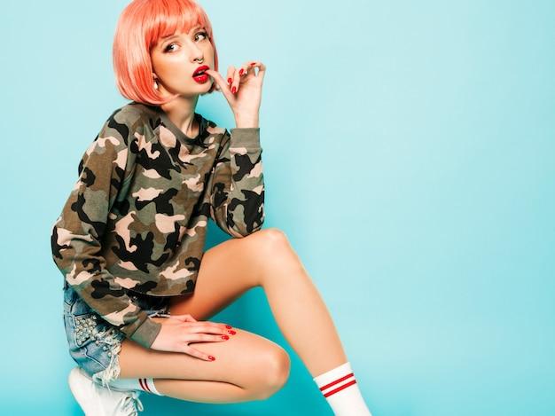 Retrato de joven hermosa chica mala inconformista en ropa de verano rojo de moda y arete en la nariz. mujer sonriente despreocupada sexy sentada en el estudio con peluca rosa cerca de la pared azul. modelo positivo divirtiéndose