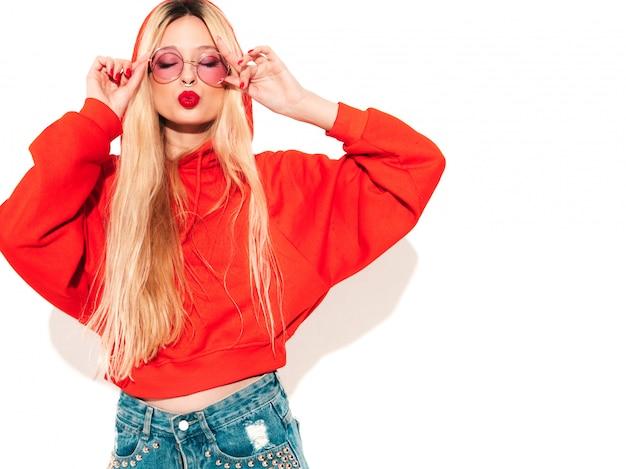 Retrato de joven hermosa chica mala inconformista en sudadera con capucha roja de moda y arete en la nariz. modelo positivo divirtiéndose aislado en blanco
