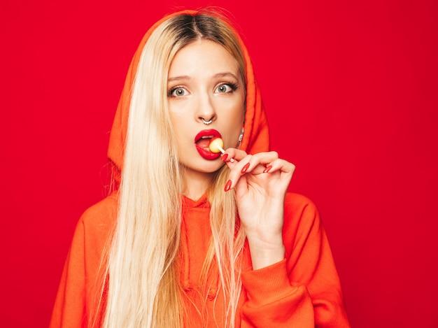 Retrato de joven hermosa chica mala inconformista en sudadera con capucha roja de moda y arete en la nariz. modelo positivo lamiendo caramelos de azúcar redondos