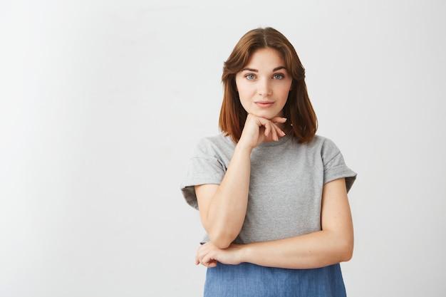 Retrato de joven hermosa muchacha posando con la mano en el mentón.