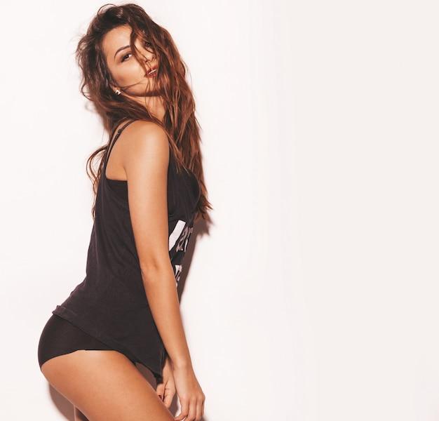 Retrato de joven hermosa muchacha sonriente hipster en moda verano negro camiseta. mujer despreocupada atractiva aislada en blanco. modelo morena con maquillaje y peinado