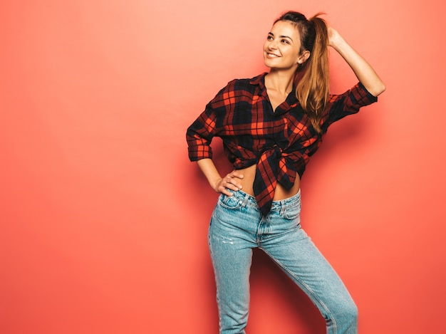 Retrato de joven hermosa muchacha sonriente hipster en ropa de jeans y camisa a cuadros de moda verano. mujer despreocupada atractiva que presenta cerca de la pared rosada en estudio. modelo positivo sin maquillaje.