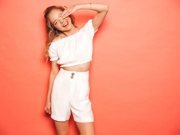 Retrato de joven hermosa muchacha sonriente hipster en ropa de moda de verano. mujer despreocupada atractiva que presenta cerca de la pared rosada. modelo positivo divirtiéndose. muestra la lengua y se cubre la cara con la mano.