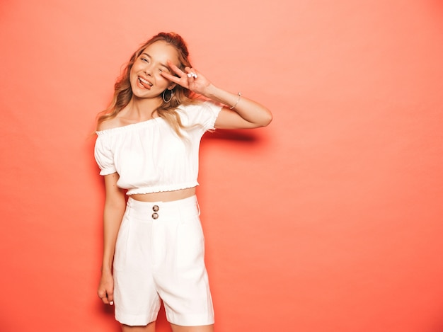 Retrato de joven hermosa muchacha sonriente hipster en ropa de moda de verano. mujer despreocupada atractiva que presenta cerca de la pared rosada. modelo positivo divirtiéndose muestra el signo de pece y la lengua