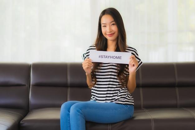 Retrato de joven hermosa muestra papel con frase quedarse en casa en el sofá