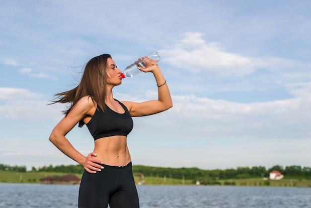 Retrato de joven hermosa mujer bebiendo agua en el parque de verano verde.