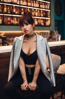 Retrato de joven hermosa mujer caucásica con cabello oscuro en chaqueta plateada, jeans negros y zapatos posa para la cámara