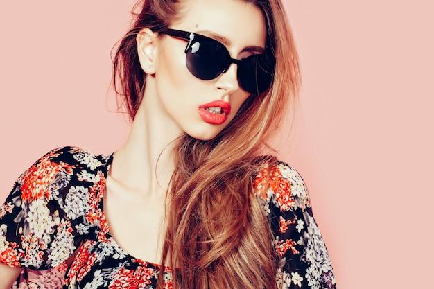 Retrato de joven hermosa mujer delgada en vestido sexy con labios sensuales con gafas de sol sonriendo y posando