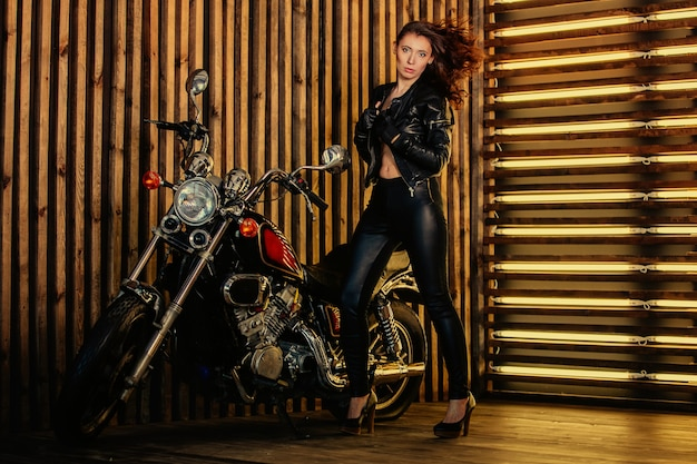 Retrato de joven hermosa mujer de moda morena sexy en chaqueta de cuero y pantalones de cuero, está de pie junto a su motocicleta