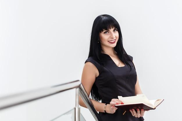 Retrato de joven hermosa mujer morena feliz trabajando con el cuaderno, de pie en una oficina, sonriendo.