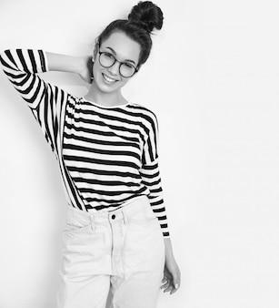 Retrato de joven hermosa mujer morena modelo chica con maquillaje desnudo en gafas en ropa hipster de verano posando junto a la pared.