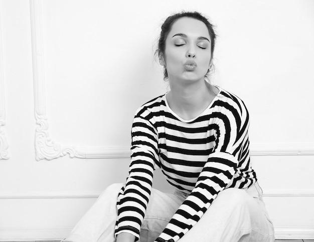 Retrato de joven hermosa mujer morena modelo chica con maquillaje desnudo en ropa hipster de verano posando junto a la pared. sentado en el suelo