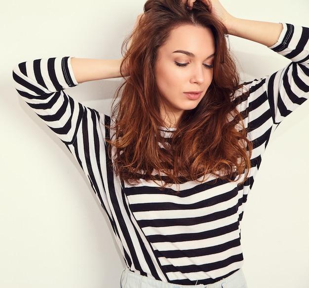 Retrato de joven hermosa mujer morena modelo chica con maquillaje desnudo en ropa hipster de verano posando junto a la pared. tocando su cabello