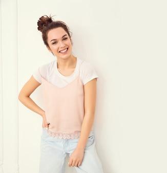 Retrato de joven hermosa mujer morena modelo chica con maquillaje desnudo en ropa de verano colorido hipster rosa posando junto a la pared. mirando felizmente