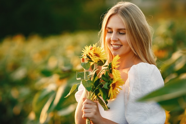 Retrato de joven hermosa mujer rubia en campo de girasoles en luz trasera. concepto de campo de verano mujer y girasoles. luz de verano. belleza al aire libre.
