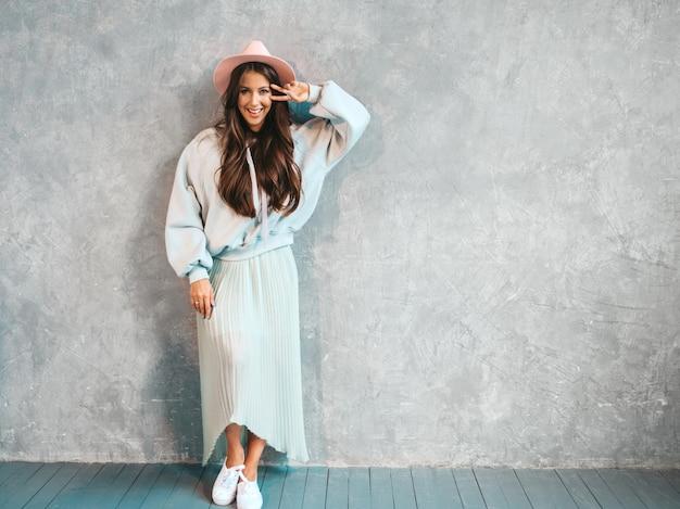 Retrato de joven hermosa mujer sonriente mirando. chica de moda en ropa casual de verano con capucha y falda.