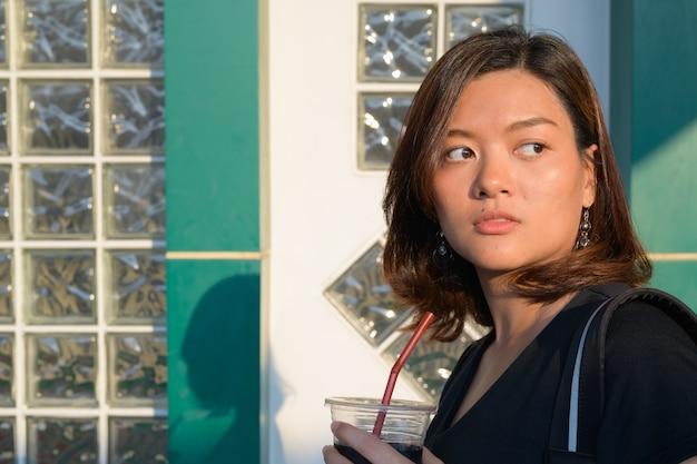 Retrato de joven hermosa mujer turista asiática con mochila en la estación de tren