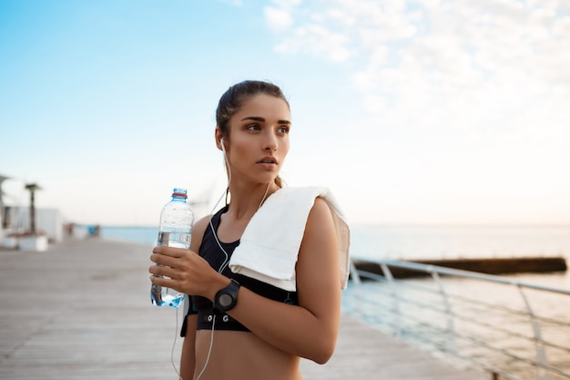 Retrato de joven hermosa niña deportiva al amanecer sobre el mar.