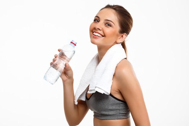 Retrato de joven hermosa niña deportiva sobre fondo blanco. agua potable