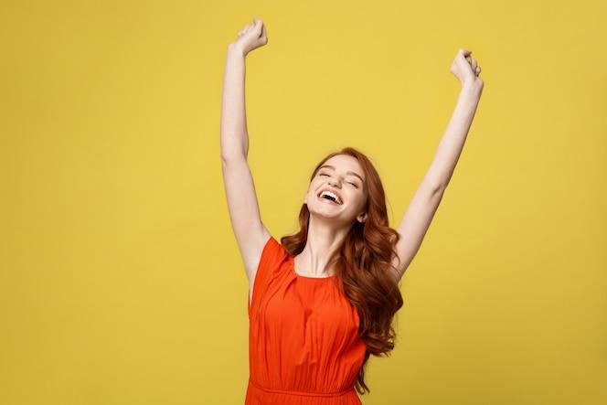Retrato joven hermosa niña feliz en naranja vestido precioso que muestra la mano en el aire.