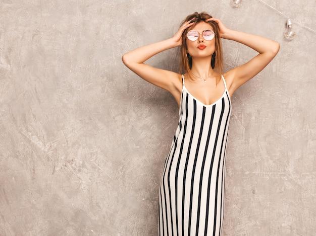 Retrato de joven hermosa niña sonriente en vestido de cebra de moda verano. mujer sexy despreocupada posando. modelo positivo divirtiéndose en gafas de sol redondas. dar beso