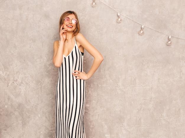Retrato de joven hermosa niña sonriente en vestido de cebra de moda verano. mujer sexy despreocupada posando. modelo positivo divirtiéndose en gafas de sol redondas