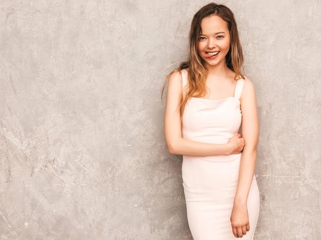 Retrato de joven hermosa niña sonriente en vestido rosa claro de moda verano. mujer sexy despreocupada posando. modelo positivo divirtiéndose y mostrando su lengua