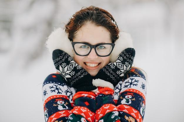 Retrato de joven hermosa con orejeras, suéter posando en el parque cubierto de nieve. mujer mirando y sonriendo