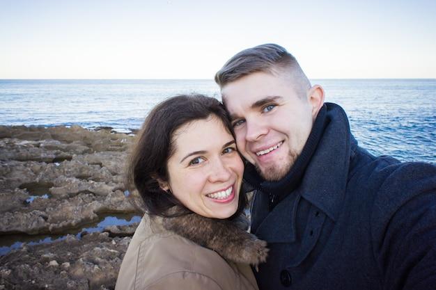 Retrato de joven hermosa pareja tomando foto selfie en un teléfono inteligente con mar y cielo nublado oscuro en el fondo. temporada fría y concepto de viaje.