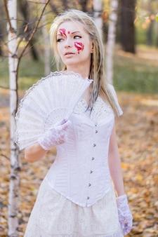 Retrato de joven hermosa con sangre maquillaje de halloween en su rostro y vestido blanco