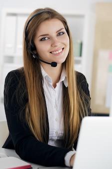 Retrato de joven hermosa sonriente trabajador de call center hablando con alguien