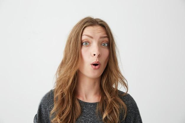 Retrato de joven hermosa sorprendida con la boca abierta.