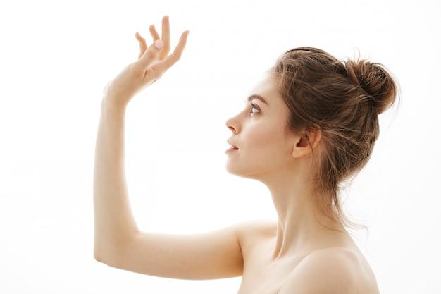 Retrato de joven hermosa tierna mujer desnuda con bollo posando en perfil sobre fondo blanco.