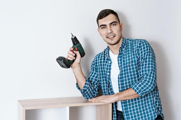 Retrato de un joven hermoso europeo con un destornillador eléctrico en la mano, un coleccionista de muebles
