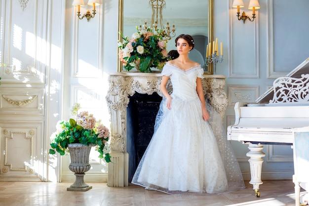 Retrato de una joven en un hermoso vestido en el interior, belleza femenina