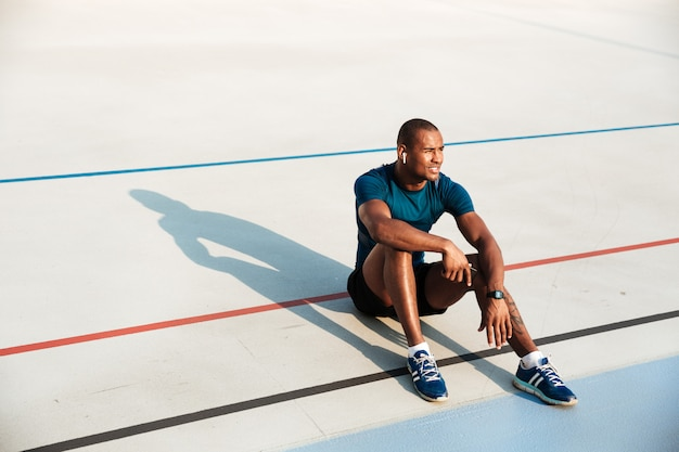 Retrato de un joven hombre africano cansado fitness en auriculares descansando