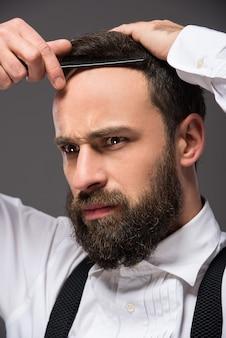 Retrato de un joven hombre barbudo brutal con navaja de afeitar.